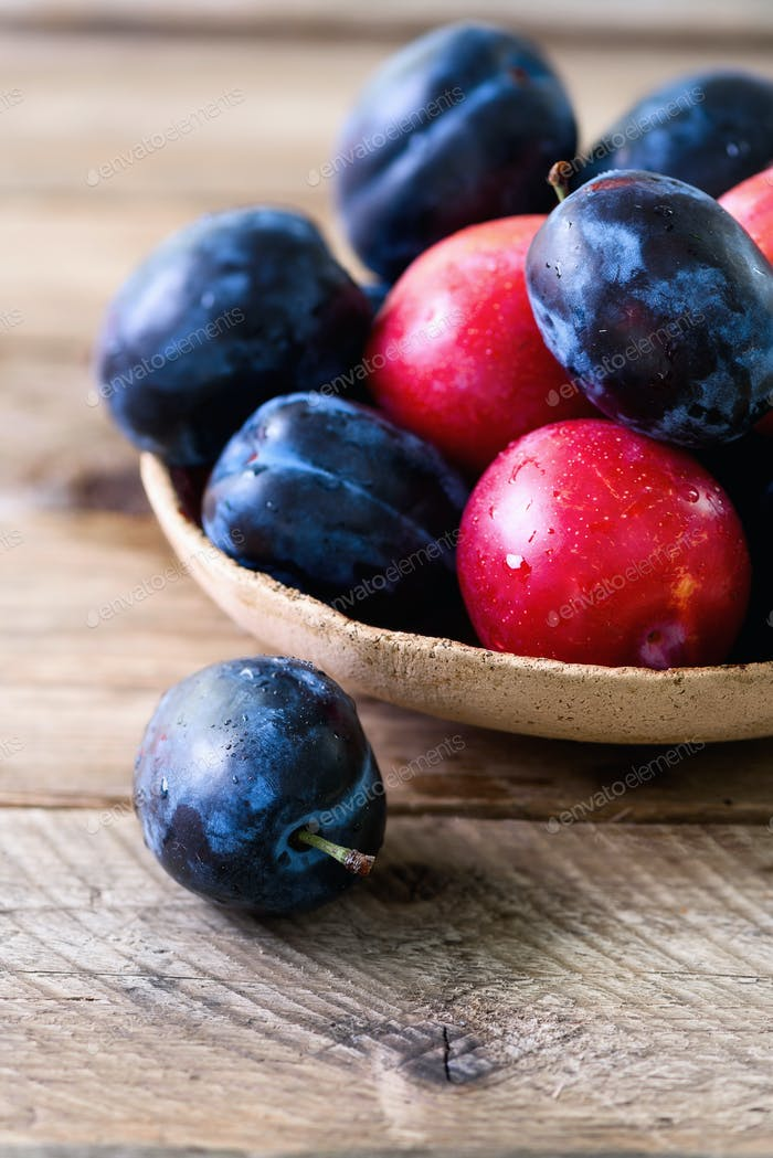 Blue and pink organic plums on dark wooden background. Copyspace