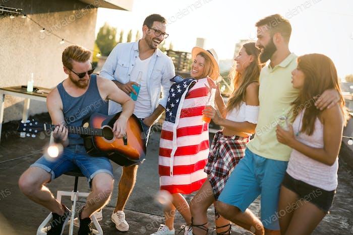 Amigos divirtiéndose y bebiendo cócteles al aire libre en una azotea se reúnen