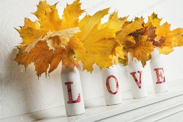 Hojas de arce amarillas en botellas con palabra amor