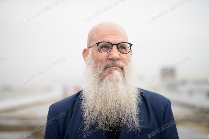 Mature handsome bald bearded businessman thinking against view of the city