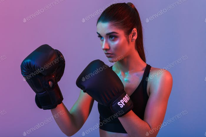 Photo closeup of focused strong woman 20s in sportive bra boxing