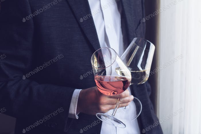 Man holding two tall glasses with wine