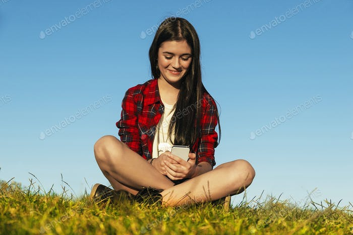 Happy Teenage Girl Using Mobile In Park