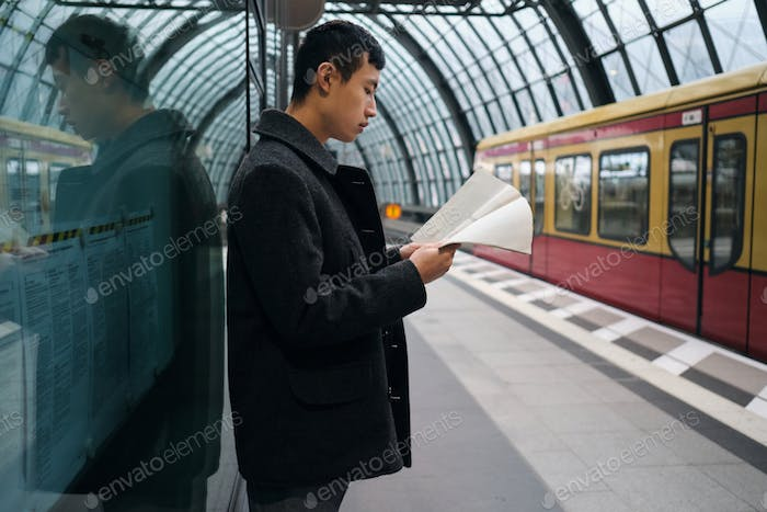 Young stylish Asian businessman confidently reading newspaper while waiting train at subway station