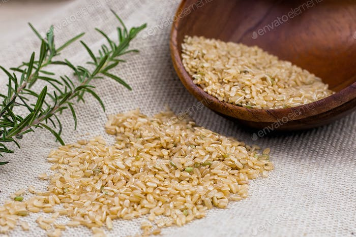 Rice grains drop out of the wooden bowl on sackcloth with rosemary