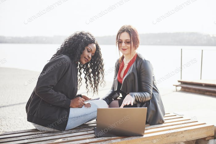 Two beautiful multi-ethnic bloggers are using the internet outdoors with their laptop