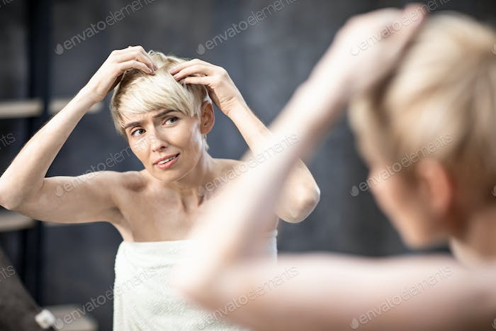 Lady Suffering From Dandruff Problem Touching Hair Standing At Home