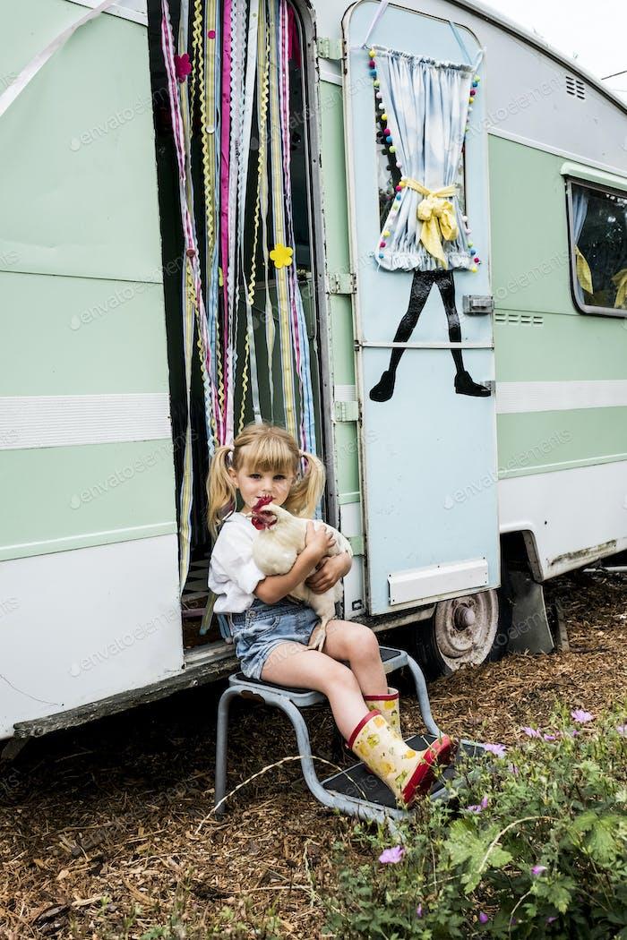 Blondes Mädchen hält weißes Huhn sitzt vor einem Wohnwagen.