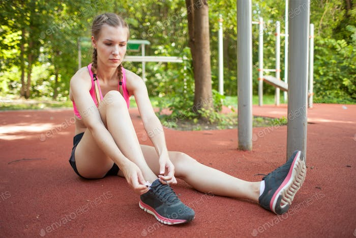 sportswoman tying shoelaces on sneakers on summer sunny sports ground