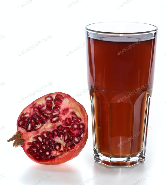 Half of pomegranate fruit and glass with juice