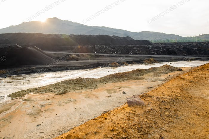 Dirty soil and polluted water on vast territory representing ecological catastrophe and desolation