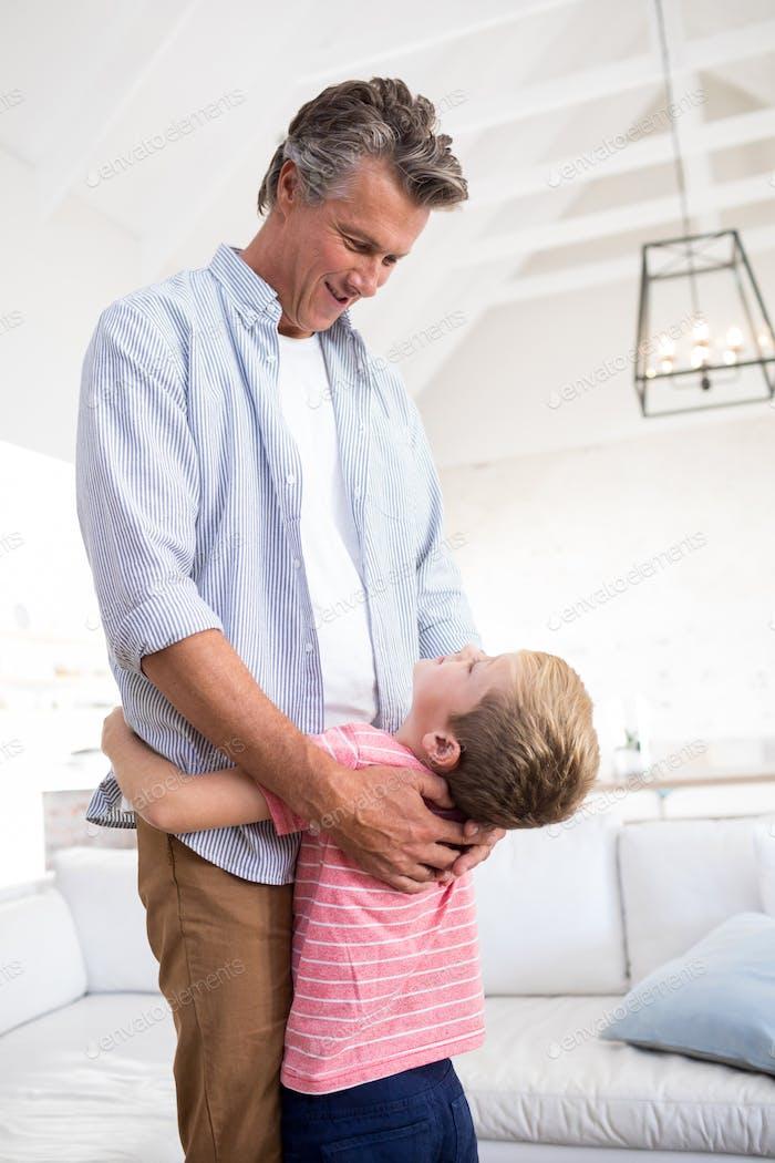 Glücklicher Vater und Sohn umarmen einander im Wohnzimmer