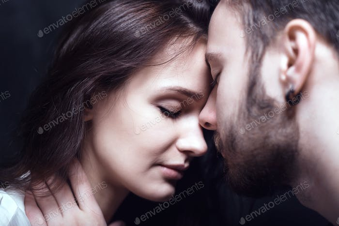 Beautiful cute loving couple in a studio with dark walls
