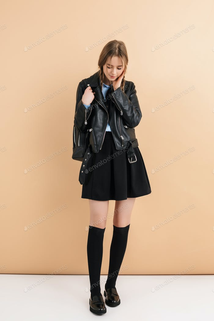 Young lady with braids in leather jacket, skirt with backpack on shoulder dreamily looking down