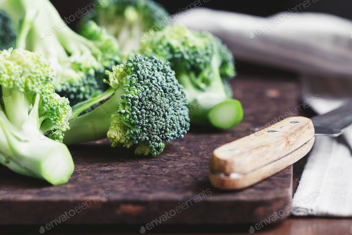 Close-up of a fresh broccoli on a cutting board. The concept of vegetarian and healthy food.