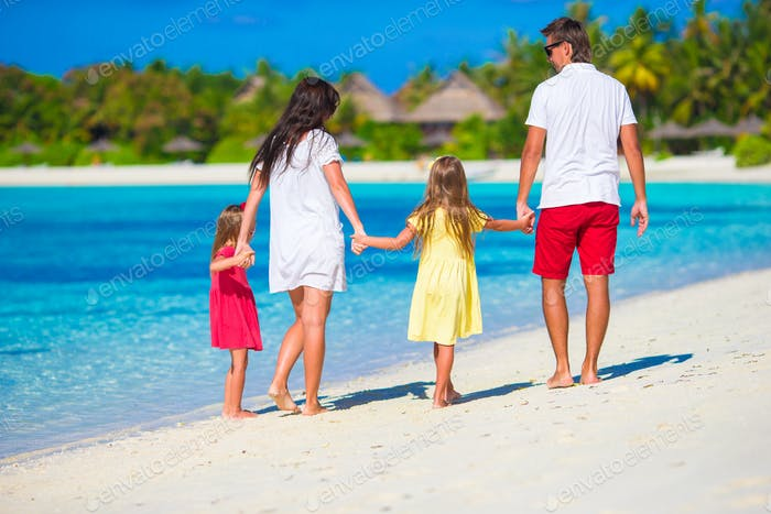 Happy family of four on white beach