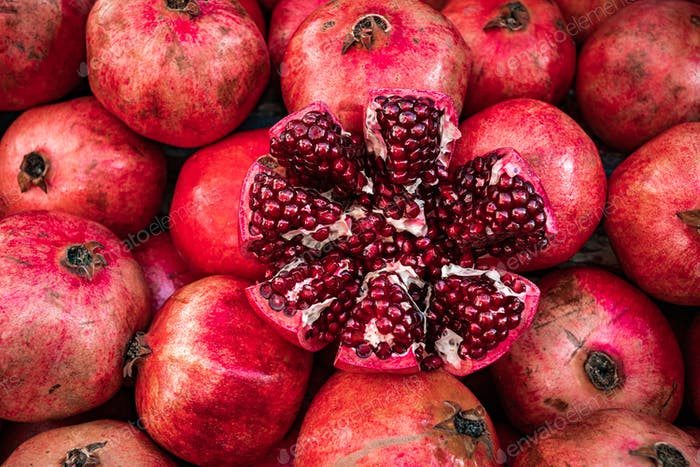 Red pomegranate fruit at street market. Group of pomegranates