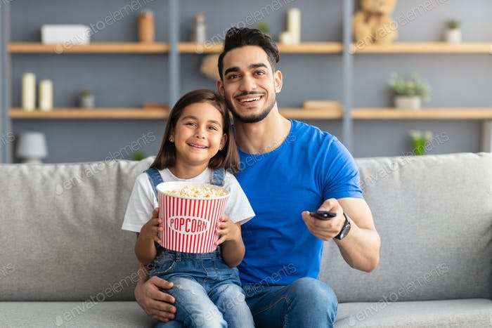 Happy loving family watching television sitting on couch