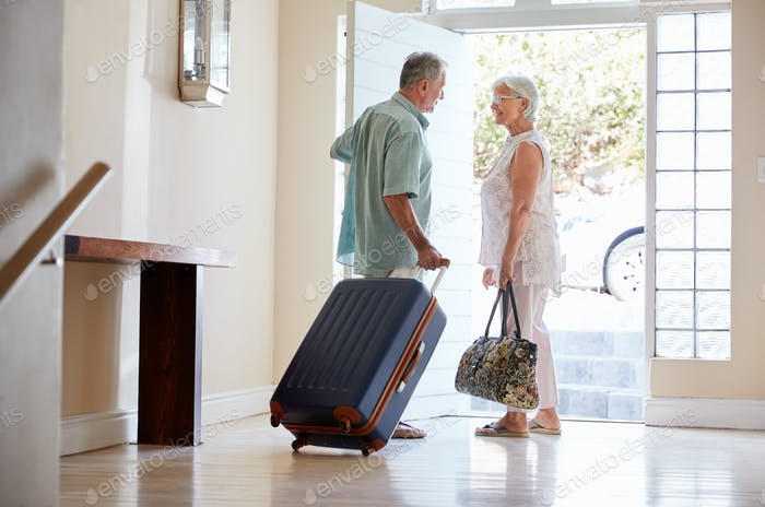 Senior Couple Standing By Front Door With Suitcase About To Leave For Vacation