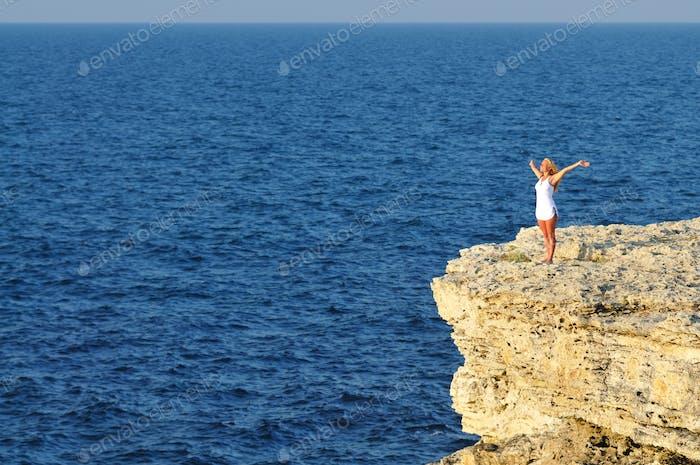 Junge Frau stehend auf Felsen über Meerwasser und Blick auf Horizont