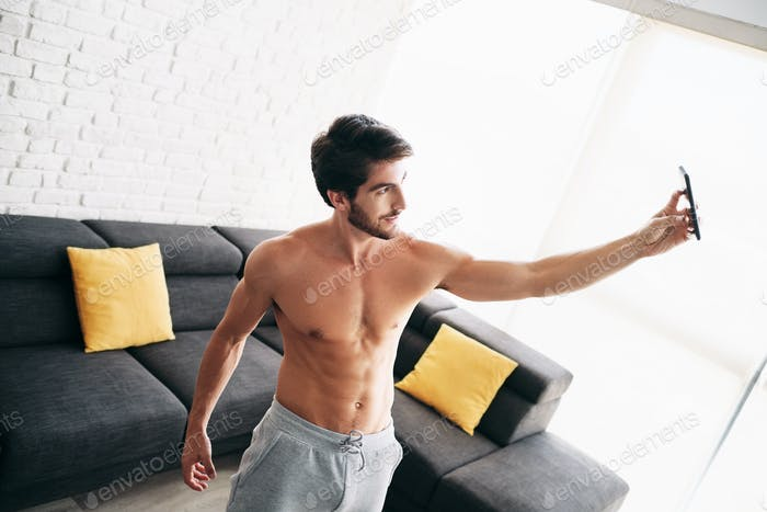 Man Working Out At Home Taking Selfie Picture With Phone