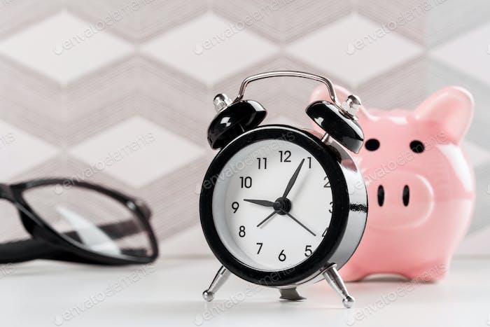 Wecker und Sparschwein-Konzept zur Zeitersparnis