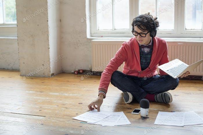Junger Mann sitzt auf dem Boden in einem Probenstudio, mit einem Laptop, Blick auf Blatt