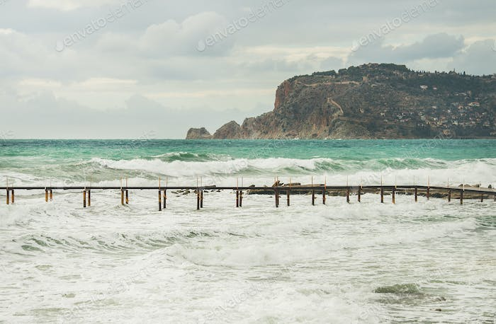 View over Alanya castle hill, stormy Mediterranean sea and pier