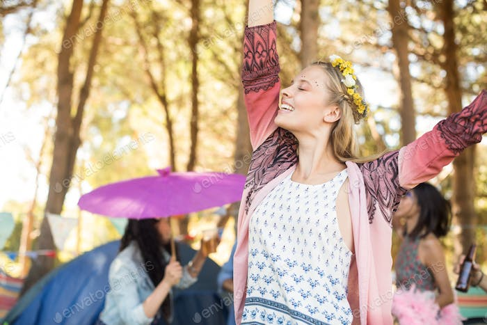 Happy woman with eyes closed raising hands at campsite