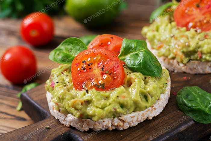Healthy breakfast. Sandwich crisp bread with guacamole and tomatoes on a wooden background.