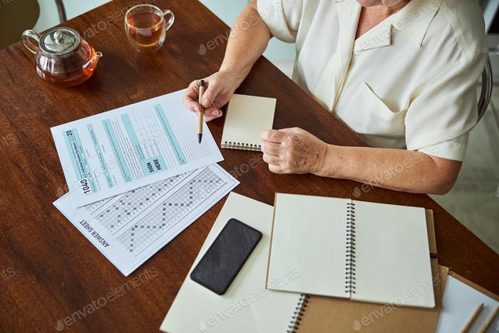 Elderly woman filling out taxes form at home