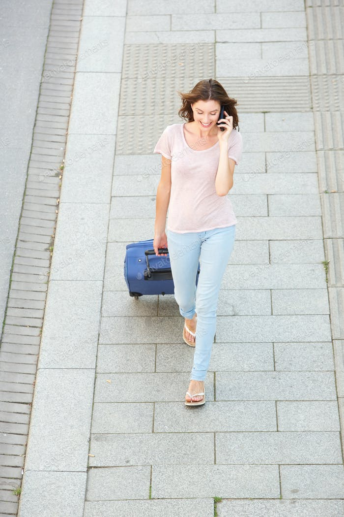woman walking with bag and talking on mobile phone
