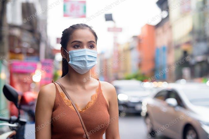 Junge asiatische Touristen Frau denken mit Maske zum Schutz vor Corona-Virus Ausbruch und Verschmutzung
