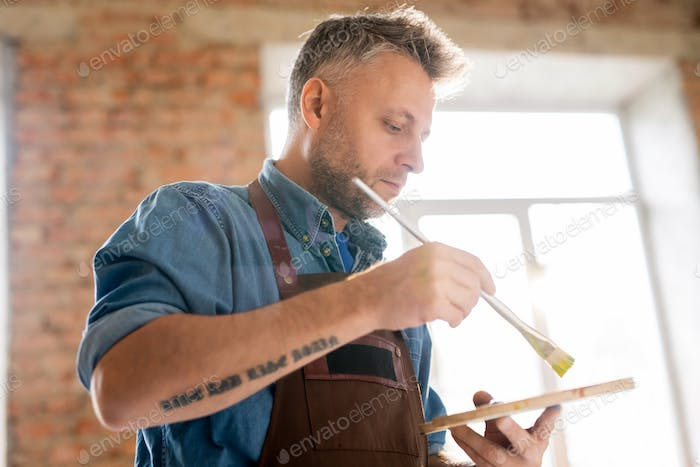 Serious mature painter in workwear mixing colors with paintbrush on palette
