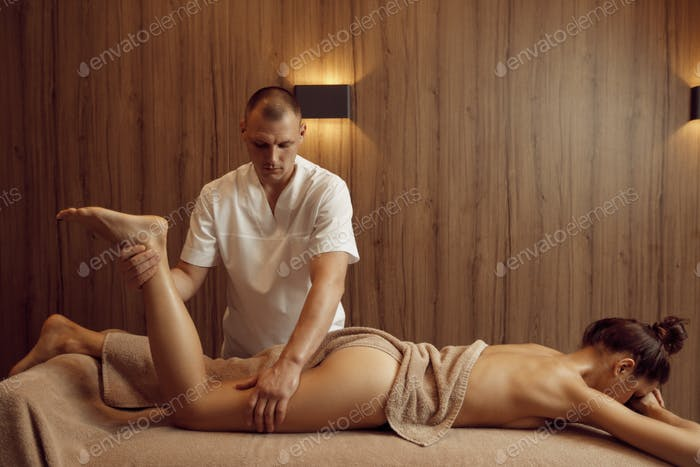Male masseur pampering legs to young woman