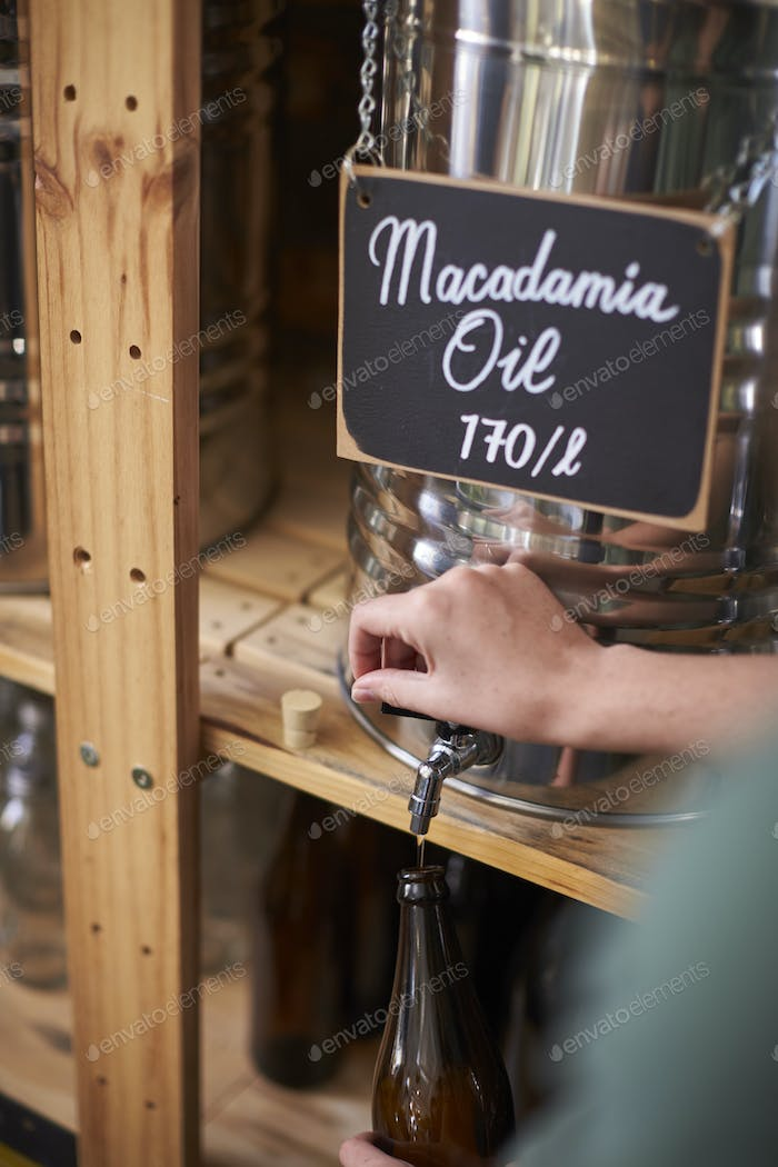 Man Filling Container With Macadamia Oil In Sustainable Plastic Free Grocery Store
