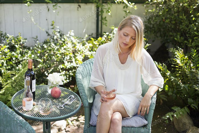 Blond woman sitting in a garden in summer, holding a wine glass.