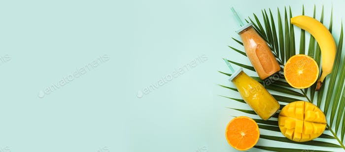 Exotic orange, banana, pineapple, mango smoothie and juicy fruits on palm leaves over blue