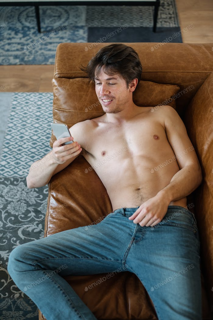 Happy man with smartphone on couch