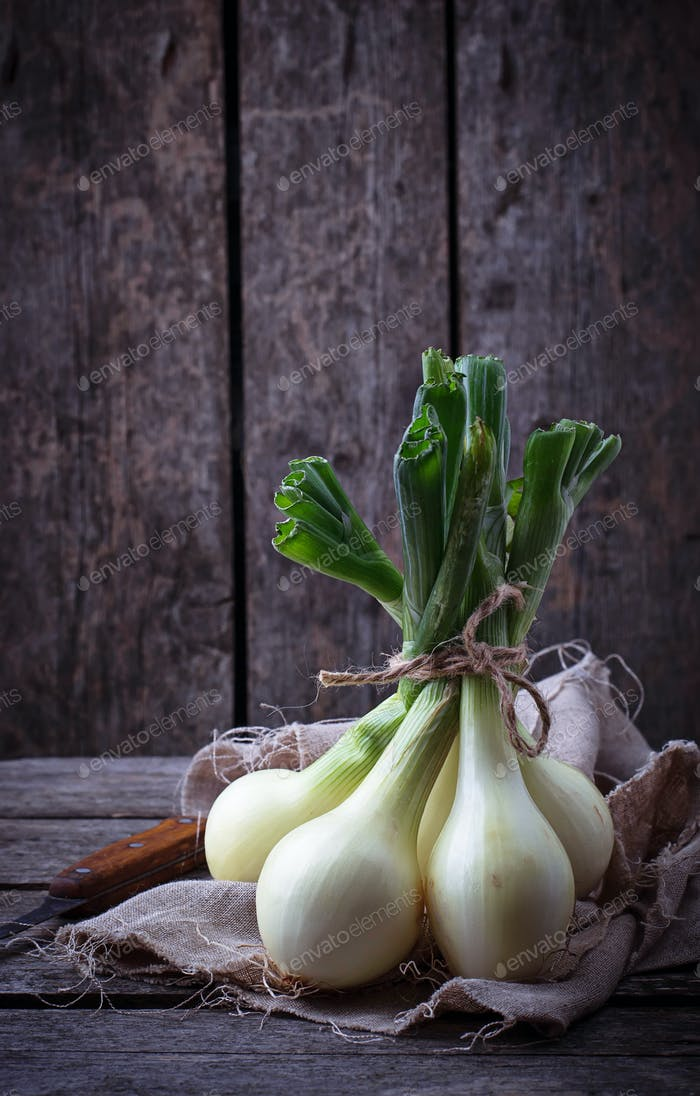 Raw fresh onions on wooden background