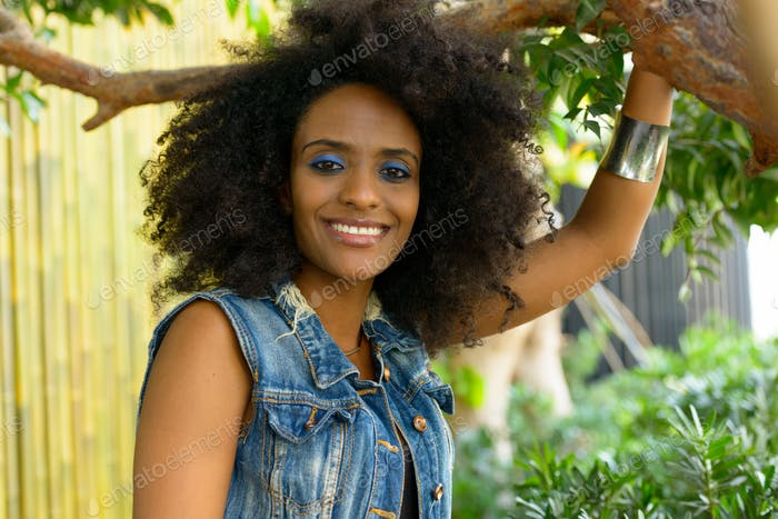 Young beautiful African woman with Afro hair at the park