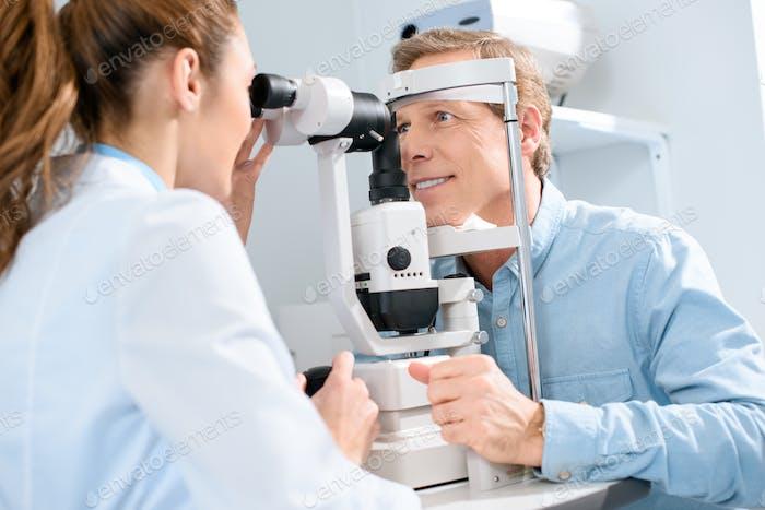 professional female optician examining man with modern visual equipment