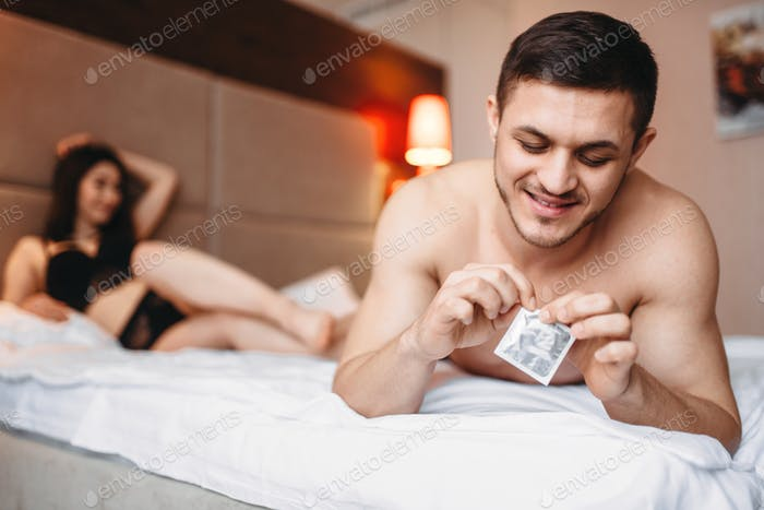 Couple lying in bed, man holds condom in his hand