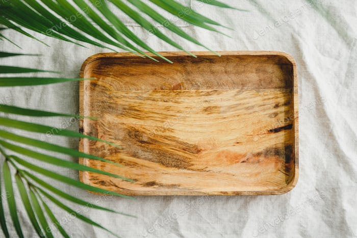 Wooden tray is made from mango tree on a linen cloth decorated palm lea