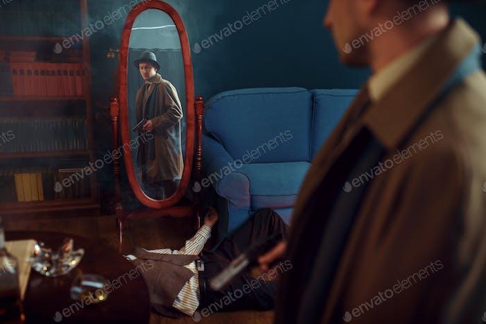 Männlicher Detektiv mit Pistole am Spiegel stehend