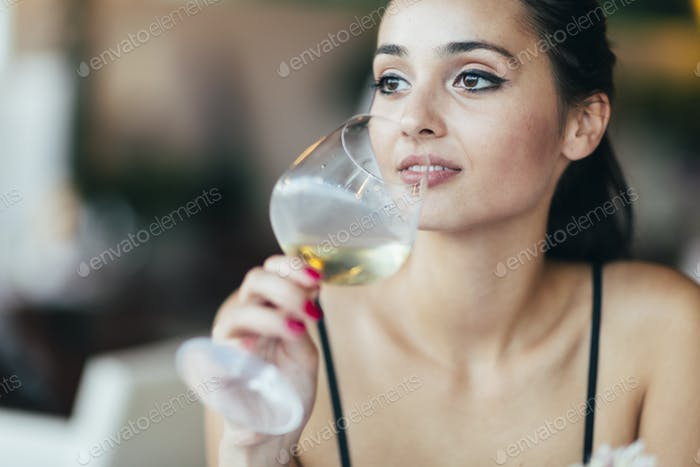 Attractive woman tasting white wine