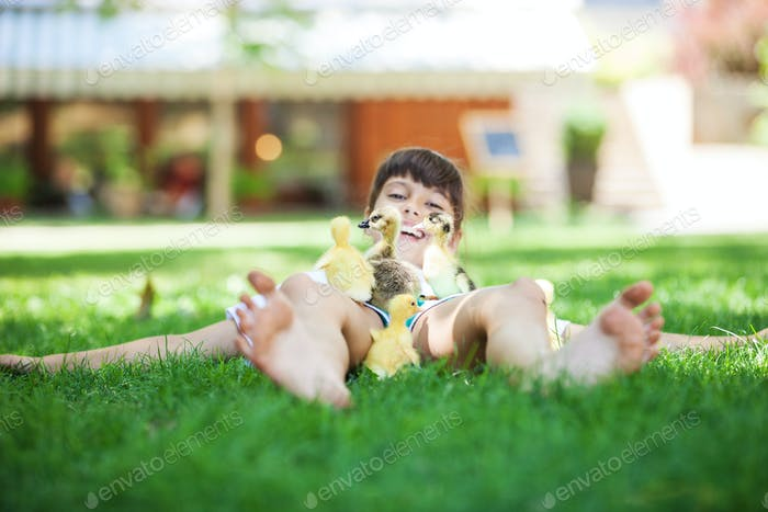 Cute girl lying down on grass and playing with spring ducklings