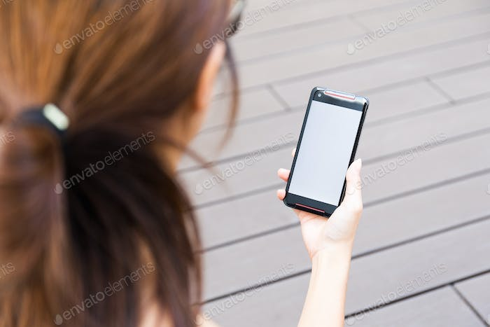 Young woman hold a smart phone with blank screen