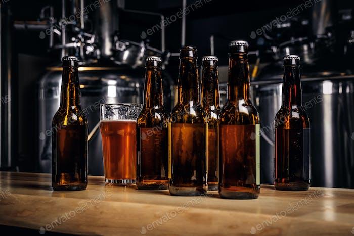 Flaschen und Glas Craft-Bier auf hölzernen Bartheke in der Indie-Brauerei.