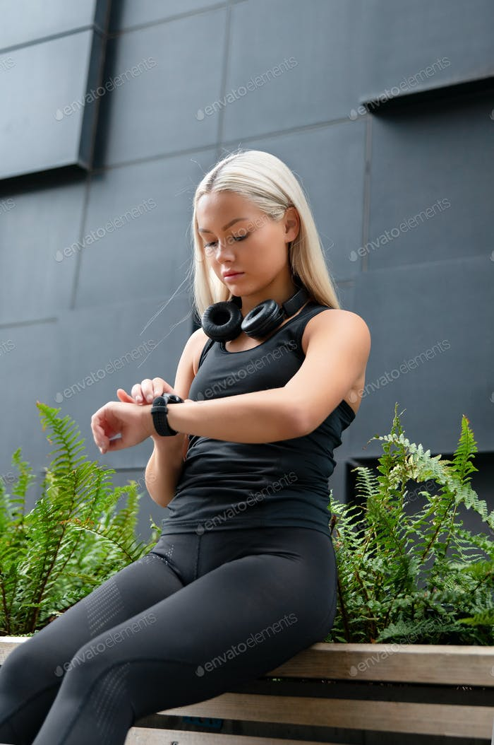 Woman Checks Workout Performance On Smart Watch in City